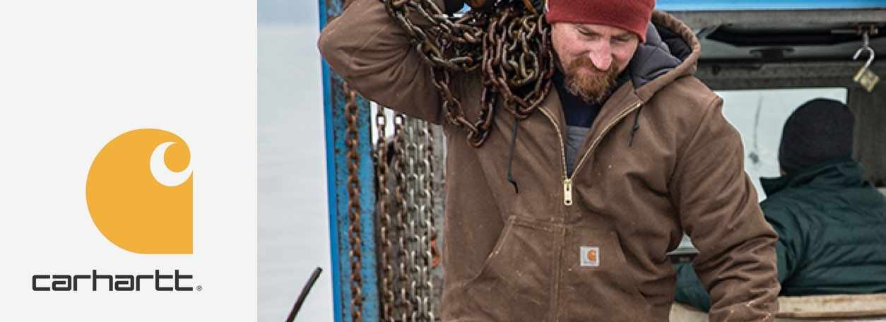 """The Carhartt """"C"""" logo next to a man in a Carhartt jacket carrying heavy chains."""